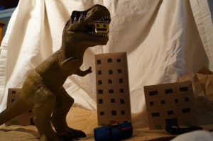 Dinosaur terrorizes cardboard city.