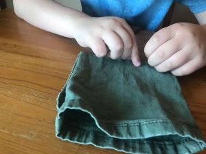 Rugrat#1 stitching the bottom of his dice bag